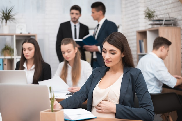 Młody kobieta w ciąży pracuje wśrodku biura