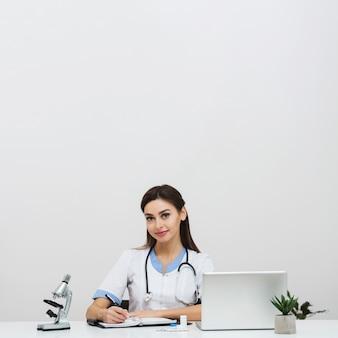 Młody kobiety lekarki obsiadanie przy biurem