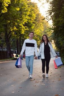 Młody kochający mężczyzna i kobieta idzie w parku. torby na zakupy w rękach. rama pionowa.