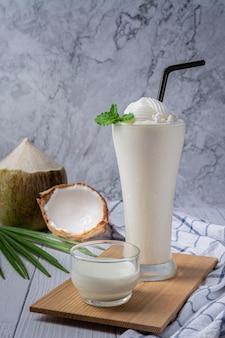 Młody koktajl z soku kokosowego w szkle, świeży słodki zdrowy koktajl z mleka kokosowego.