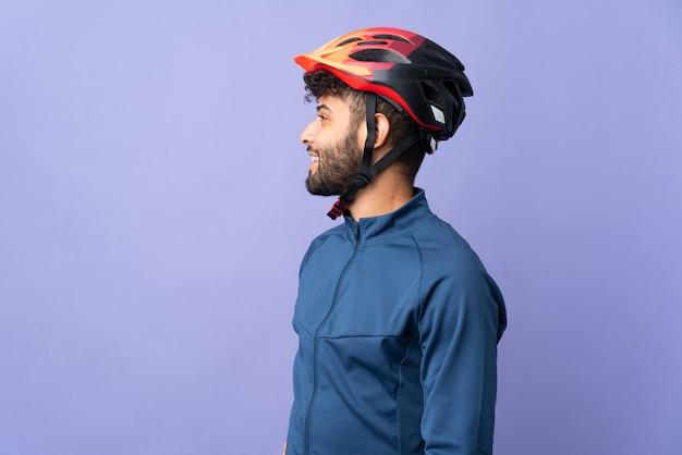 Młody kolarz marokański mężczyzna na białym tle na fioletowy śmiejąc się w pozycji bocznej