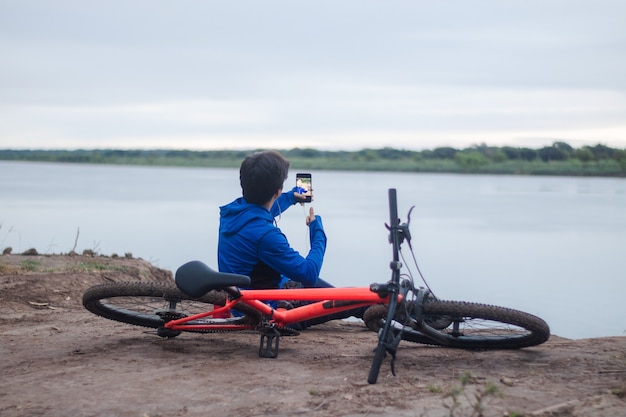 Młody kolarz robi sobie selfie, odpoczywa na ziemi obok swojego roweru, aktywny tryb życia.