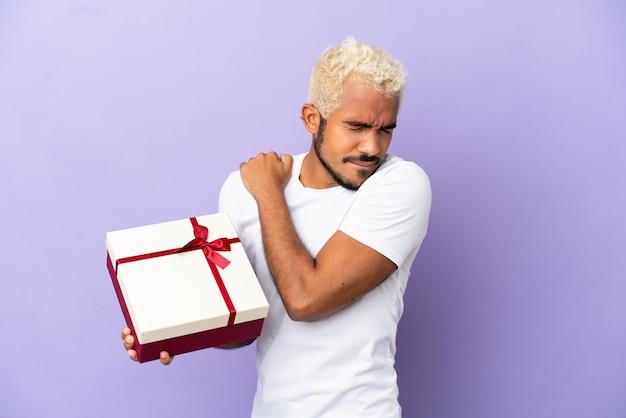 Młody kolumbijczyk trzymający prezent na białym tle na fioletowym tle cierpiący na ból w ramieniu za wysiłek