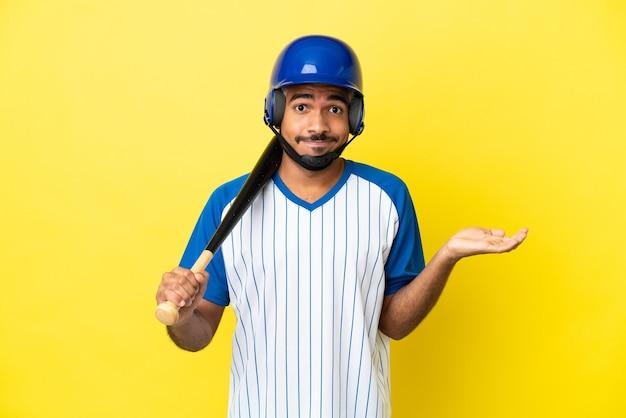 Młody kolumbijski latynoski mężczyzna grający w baseball na żółtym tle, mający wątpliwości podczas podnoszenia rąk