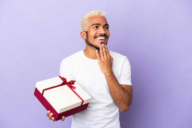 Młody kolumbijski mężczyzna trzymający prezent na białym tle na fioletowym tle patrząc w górę podczas uśmiechania się