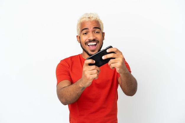 Młody kolumbijski przystojny mężczyzna na białym tle bawi się telefonem komórkowym