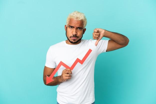 Młody kolumbijski przystojny mężczyzna na niebieskim tle trzyma strzałkę w dół i robi zły sygnał