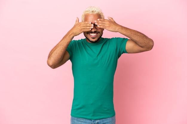 Młody kolumbijski przystojny mężczyzna odizolowany na różowym tle zakrywający oczy rękami i uśmiechnięty