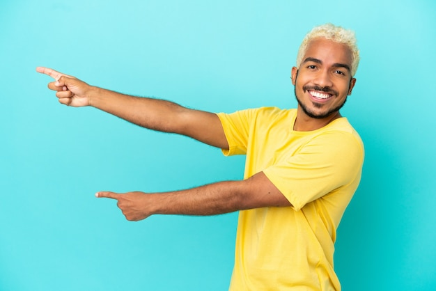 Młody kolumbijski przystojny mężczyzna odizolowywający na niebieskim tle wskazujący palec w bok i prezentujący produkt
