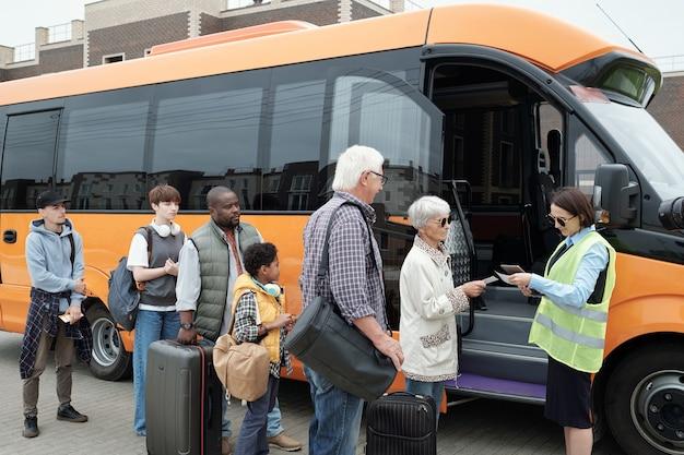Młody konduktor autobusowy sprawdzający bilety przy otwartych drzwiach pojazdu