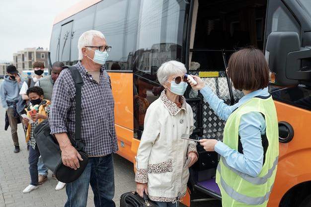 Młody konduktor autobusowy sprawdzający temperaturę ciała pasażerów