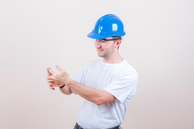 Młody konstruktor ma palec ze szczypcami w koszulce, kasku i wygląda na rozbawionego