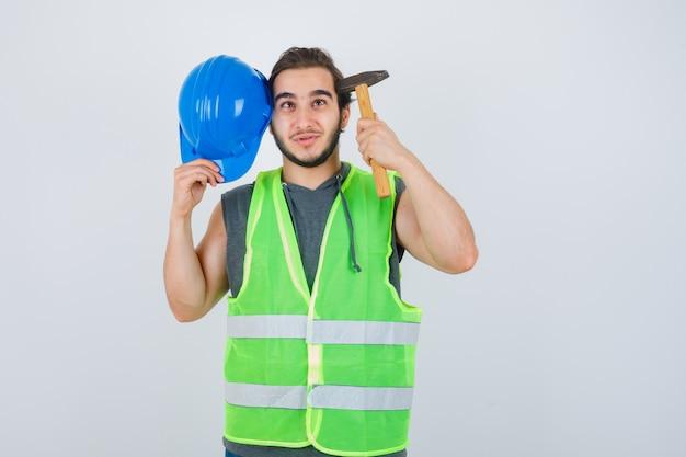Młody konstruktor mężczyzna trzyma młotek i hełm nar głowy w mundurze odzieży roboczej i patrząc wesoło, widok z przodu.