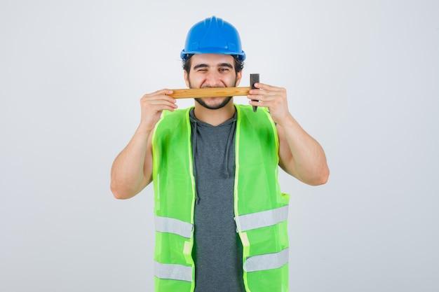 Młody konstruktor mężczyzna trzyma młotek na ustach w mundurze i wygląda uroczo. przedni widok.