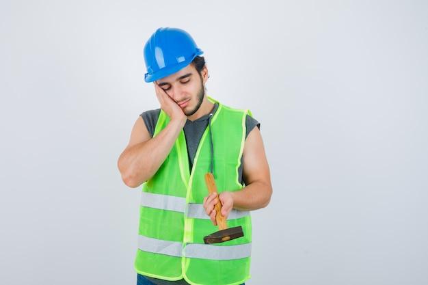 Młody konstruktor mężczyzna trzyma młotek, opierając policzek pod ręką w mundurze odzieży roboczej i patrząc zamyślony, widok z przodu.