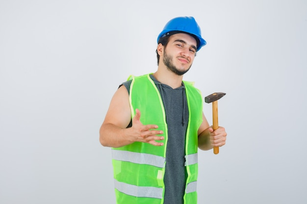 Młody konstruktor mężczyzna trzyma młotek w mundurze i wygląda pewnie, widok z przodu.