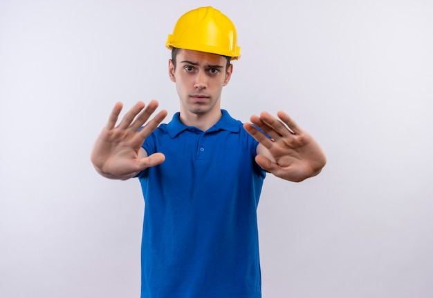 Młody konstruktor mężczyzna ubrany w mundur budowy i hełm ochronny robi gest stopu rękami