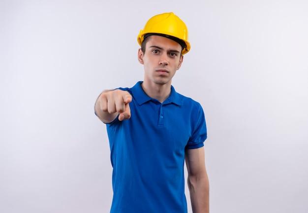Młody konstruktor mężczyzna ubrany w mundur konstrukcyjny i hełmy ochronne z palcem wskazującym
