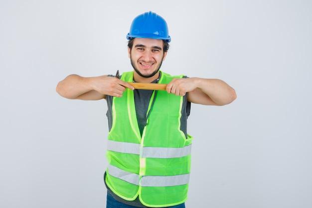 Młody konstruktor mężczyzna w mundurze odzieży roboczej, trzymając młotek i patrząc wesoło, widok z przodu.