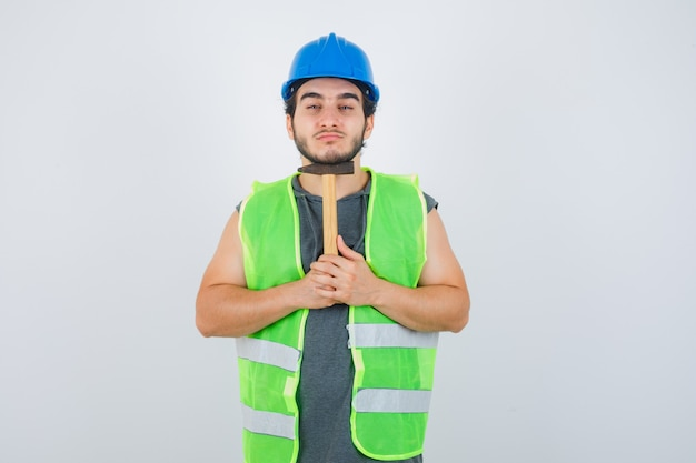 Młody konstruktor mężczyzna w mundurze odzieży roboczej trzymając młotek pod brodą i patrząc pewnie, z przodu.