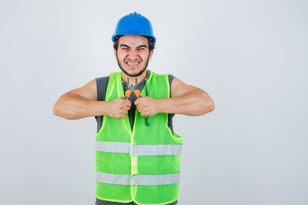 Młody konstruktor mężczyzna w mundurze odzieży roboczej, trzymając szczypce i patrząc szczęśliwy, widok z przodu.