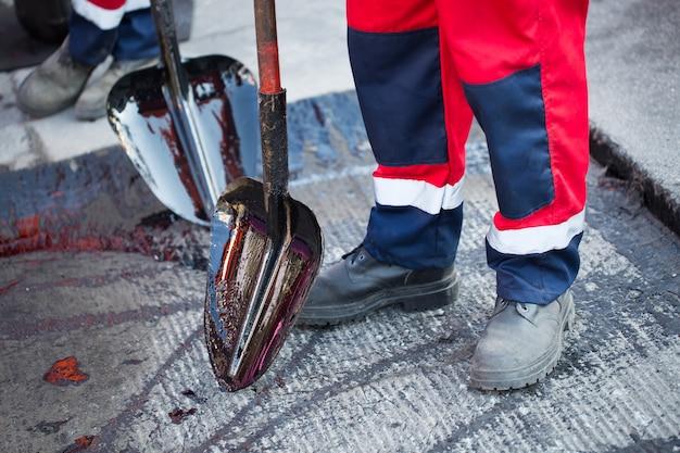 Młody konstruktor na maszynie do asfaltowania podczas remontu ulic drogowych