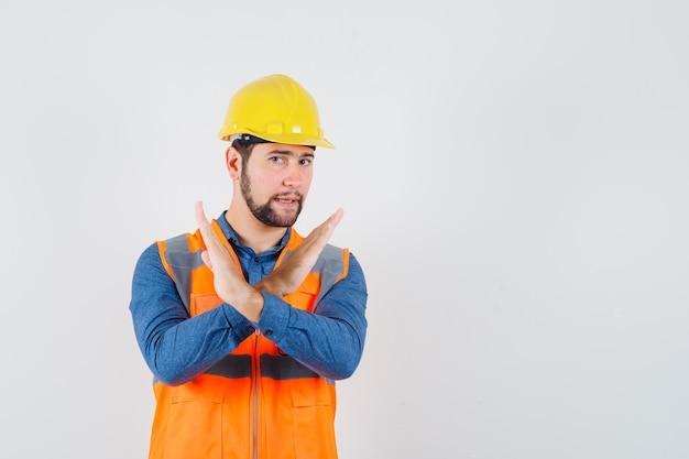 Młody konstruktor pokazuje gest stopu w koszuli, kamizelce, kasku i wygląda na zirytowanego. przedni widok.
