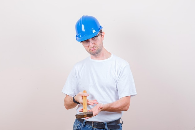 Młody konstruktor trzymający młotek w koszulce, dżinsach, kasku i niezdecydowany