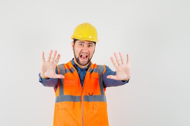 Młody konstruktor w koszuli, kamizelce, hełmie, pokazujący gest stop, krzyczący i przestraszony, widok z przodu.