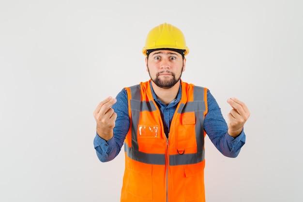 Młody konstruktor w koszuli, kamizelce i kasku, próbuje coś wyjaśnić i wygląda na zmartwionego, widok z przodu.