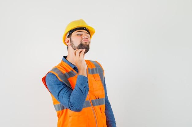 Młody konstruktor w koszuli, kamizelce, kasku drapie się po brodzie i wygląda elegancko, widok z przodu.