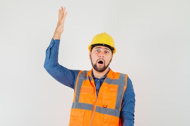 Młody konstruktor w koszuli, kamizelce, kasku podnoszącym rękę i wyglądającym na zszokowanego, widok z przodu.