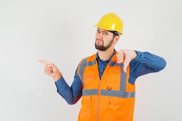 Młody konstruktor w koszuli, kamizelce, kasku, pokazujący kciuk w dół, wskazujący na bok i niezadowolony, widok z przodu.