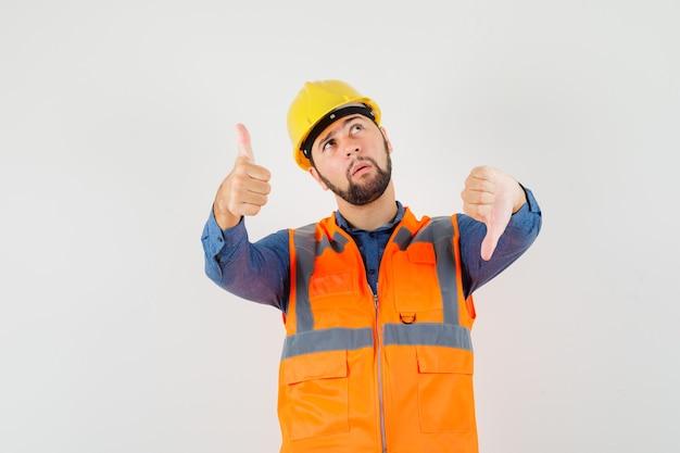 Młody konstruktor w koszuli, kamizelce, kasku, pokazujący kciuki w górę iw dół i niepewnie wyglądający, widok z przodu.