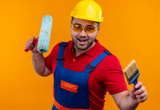 Młody konstruktor w mundurze budowlanym i hełmie ochronnym, trzymając wałek do malowania i pędzel, uśmiechając się radośnie