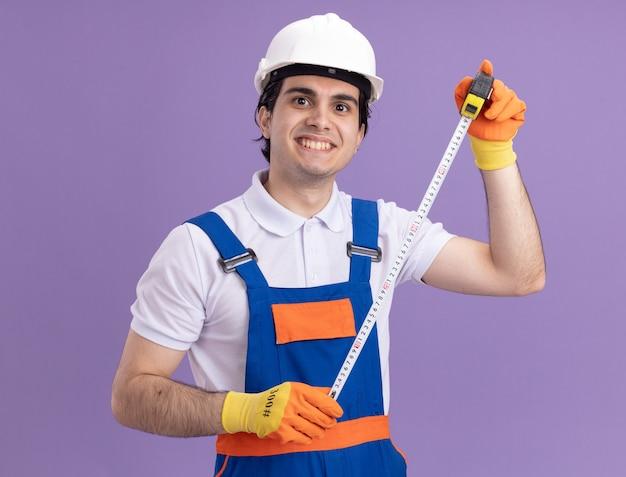 Młody konstruktor w mundurze budowlanym i hełmie ochronnym w gumowych rękawiczkach, trzymając taśmę mierniczą patrząc z przodu z uśmiechem na twarzy stojącej nad fioletową ścianą