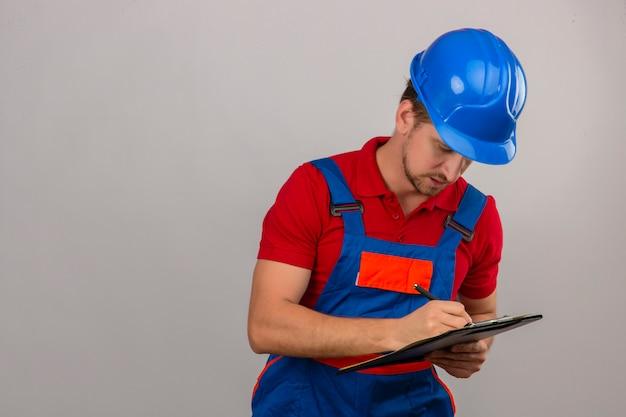 Młody konstruktor w mundurze budowy i hełmie ochronnym, pisząc w schowku na pojedyncze białe ściany