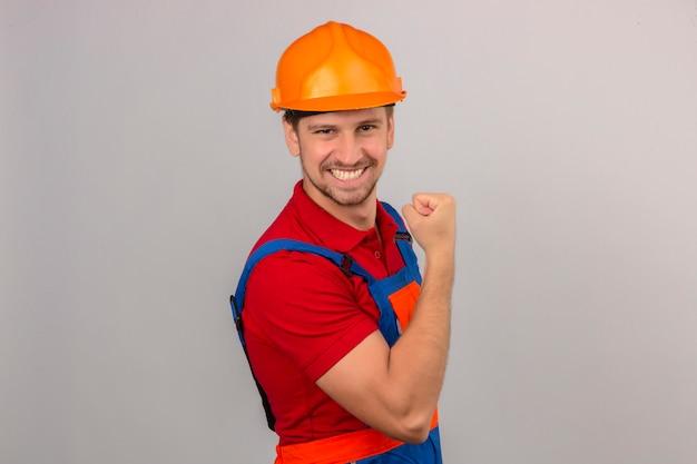 Młody konstruktor w mundurze budowy i hełmie ochronnym pokazując bicepsy na dłoni uśmiechnięta koncepcja zwycięzcy na izolowanych białej ścianie