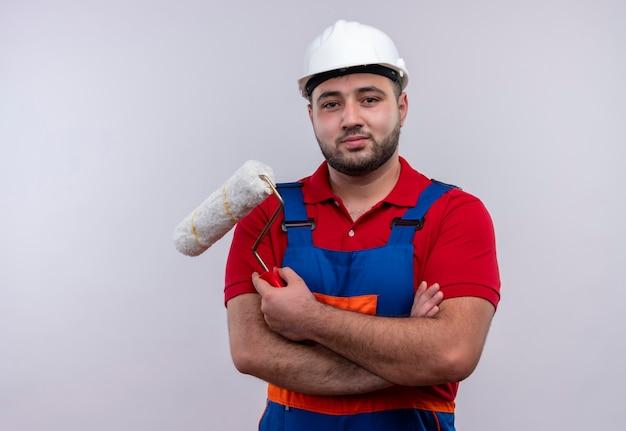Młody konstruktor w mundurze budowy i hełmie ochronnym, trzymając kufel rolki wirh ramiona skrzyżowane patrząc na kamery z poważną twarzą