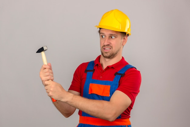 Młody konstruktor w mundurze budowy i hełmie ochronnym, trzymając młotek i patrząc na to z sceptycznym wyrazem twarzy na izolowanych białej ścianie