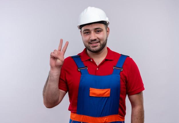 Młody konstruktor w mundurze budowy i hełmie ochronnym, uśmiechając się, pokazując i wskazując palcami numer dwa