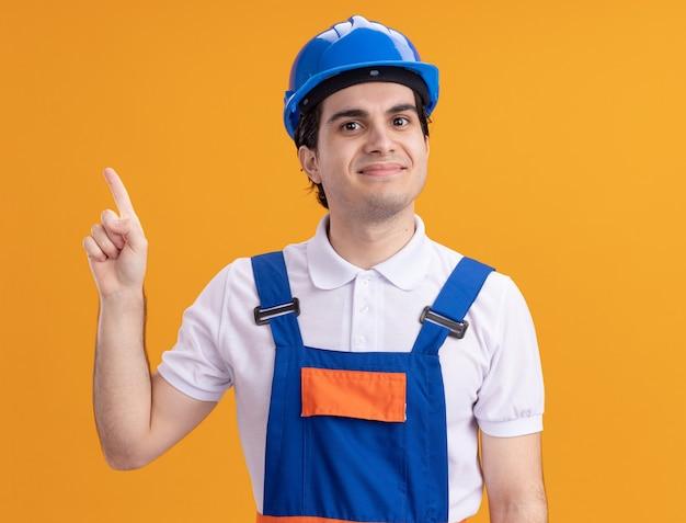 Młody konstruktor w mundurze budowy i kasku ochronnym patrząc na przód uśmiechnięty pewnie wskazując palcem wskazującym, stojąc nad pomarańczową ścianą
