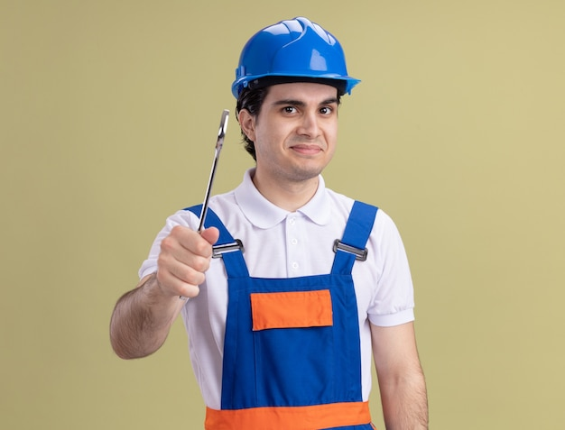 Młody konstruktor w mundurze budowy i kasku ochronnym trzymając klucz patrząc na przód uśmiechnięty stojący nad zieloną ścianą