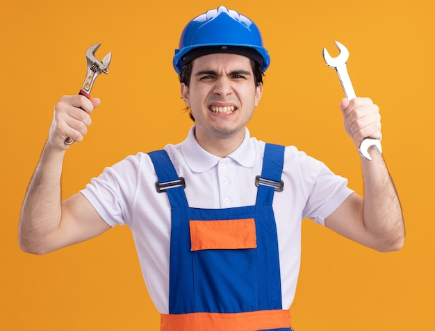 Młody konstruktor w mundurze budowy i kasku ochronnym, trzymając klucze patrząc z przodu z gniewną twarzą stojącą nad pomarańczową ścianą