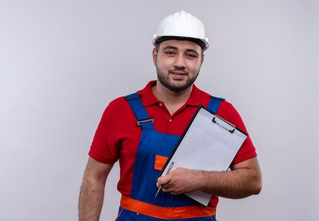 Młody konstruktor w mundurze budowy i kasku ochronnym trzymając schowek patrząc na kamery z uśmiechem na twarzy