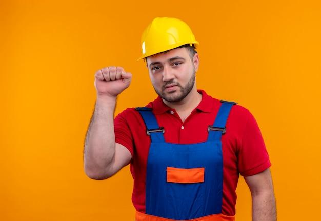Młody konstruktor w mundurze budowy i kasku ochronnym zaciskając pięść patrząc na kamery z poważną miną