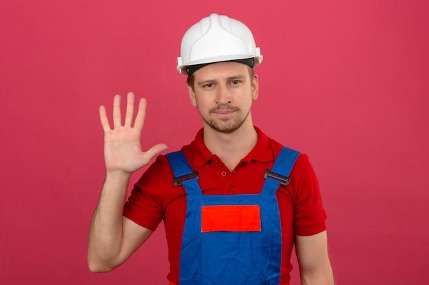 Młody konstruktor w mundurze konstrukcyjnym i hełmie ochronnym pokazując i wskazując palcami numer pięć z uśmiechem na twarzy nad izolowaną różową ścianą