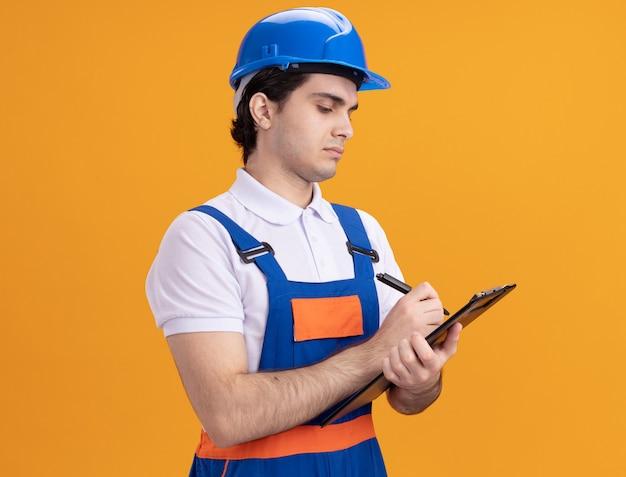 Młody konstruktor w mundurze konstrukcyjnym i hełmie ochronnym, trzymając schowek, pisząc piórem, patrząc pewnie stojąc nad pomarańczową ścianą
