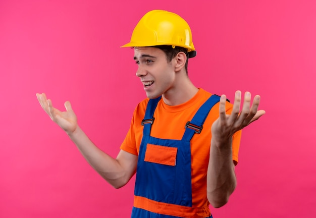Młody konstruktor w mundurze konstrukcyjnym i kasku ochronnym jest zaskoczony