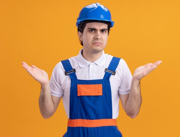 Młody konstruktor w mundurze konstrukcyjnym i kasku ochronnym patrząc z przodu zdezorientowany i niezadowolony z podniesionymi rękami stojącymi nad pomarańczową ścianą